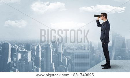 Businessman looking forward to a city  with binoculars from skyscraper concept