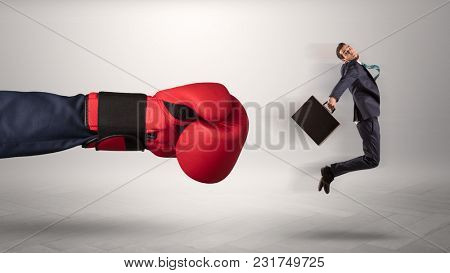 Giant hand gives a kick to a small employee businessman