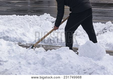 Cleaning The Snow With A Shovel After A Heavy Snowfall. A Man Removes Snow On A City Street