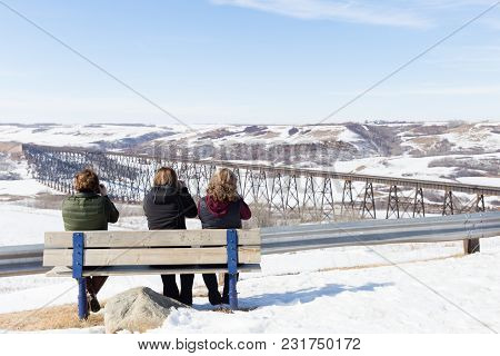 Horizontal Image Of Three Women Sitting On A Bench In The Winter Time Photographing The Scene Ahead