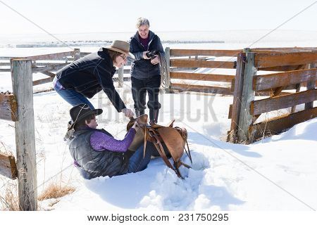 Horizontal Image Of Three Caucasian Women Laughing As One Trips And Falls Into The Snow Bank While C