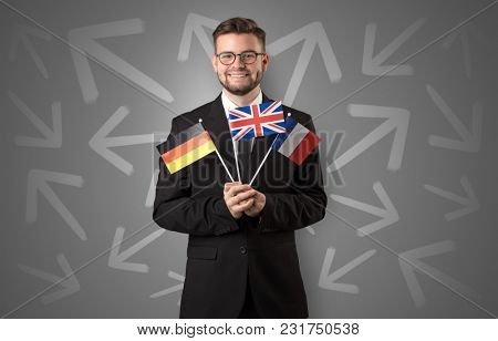 Cheerful elegant boy standing with flag on his hand and chalk drawn arrows around