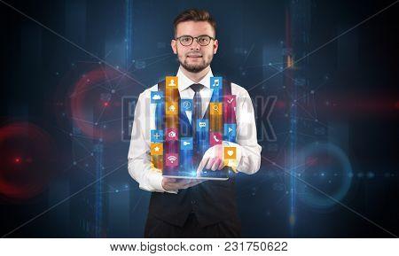 Elegant businessman holding tablet with hologram application icons and symbols above
