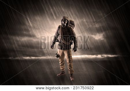 Terrorist in a stormy space with gas mask on his hand and weapons on his arm