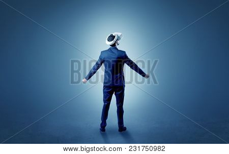 Businessman wearing vr glasses in an empty room with no wallpaper