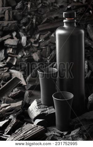 Original Black Matte Bottle Of Vodka Or Tequila And Black Shot Glass .on Charcoal Background. Black
