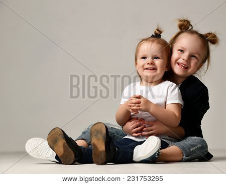 Beautiful Little Sisters Girls Kids Sitting Together Hugging Happy Smiling On Gray Background