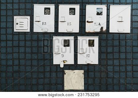 A Tiledteal Wall With The Multiple Electricity Supply Meters And Switchboards On It Hidden Under Th