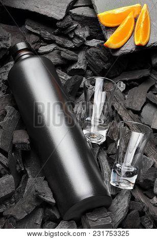 Original Black Matte Bottle Of Vodka Or Tequila And Shot Glass .slices Of Oranges.on Charcoal Backgr