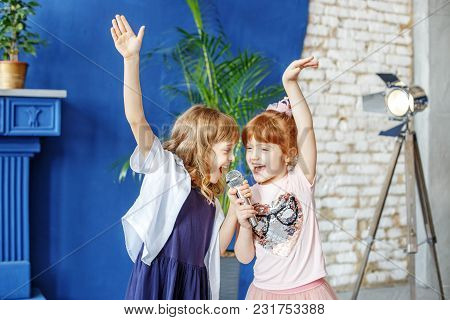 Two Little Funny Children Dance And Sing A Song In Karaoke. The Concept Is Childhood, Lifestyle, Mus