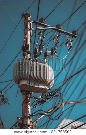 Vertical Shot Of An Electric Power Pole With A High-voltage Transformer Unit Surrounded By Heat Sink