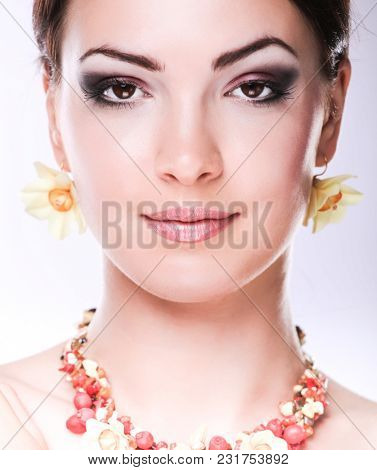 Portrait of young beautiful brunette woman in beads