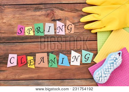 Accessories For Cleaning On Wooden Background. Cut Out Colorful Letters Spring Cleaning On Wooden Fl