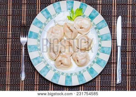 Appetizing Boiled Perogies With Sour Cream On A Large Beautiful Plate With A Green Fresh Leaf, A Met