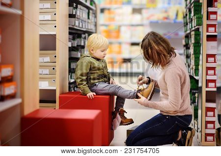 Cute Little Boy During Shopping With His Young Mother. Kid Trying New Fashion Seasonal Shoes. Child