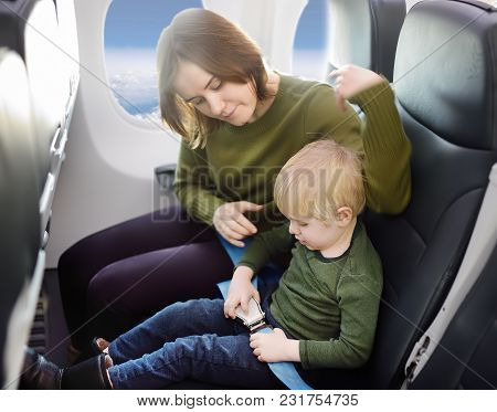 Young Mother Helping Her Little Son With Safety Belt During Traveling By An Airplane. Traveling With