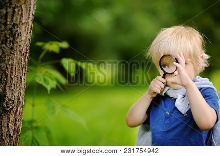 Funny Kid Exploring Nature With Magnifying Glass. Little Boy Looking At Tree With Magnifier. Summer