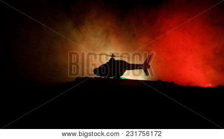 Silhouette Of Military Helicopter Ready To Fly From Conflict Zone. Decorated Night Footage With Heli