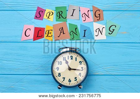 Time For Clean Up For Spring. Blue Alarm Clock And Colorful Letters Spring Cleaning. Time For Spring