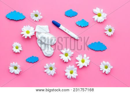 Pregnancy Test, Socks And Flowers On Pink Background Top View