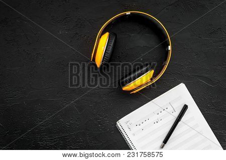 Composer Office Desk . Workplace Of Musician With Headphones And Notes Black Background Top View Moc