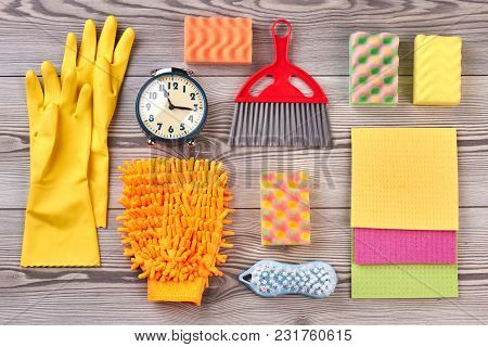 Spring Cleaning Background With Supplies. Close Up Colorful House Cleaning Products And Alarm Clock.