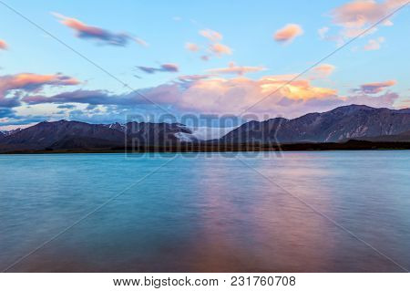 Beautiful dramatic sunset over the incredibly blue lake Tekapo with clouds quickly flowing from the mountains. Canterbury region, New Zealand