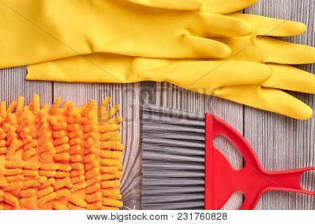 Close Up Gloves And Brush For Cleaning. House Cleaning Items On Wooden Background.