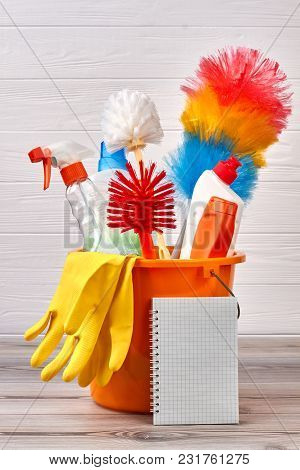 Different Objects For Cleaning In Bucket. Colorful Cleaning Brushes And Detergents On Wooden Backgro