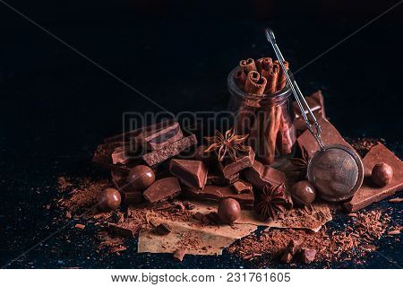 Header With Cinnamon In A Glass Jar, Scattered Cocoa Powder And Pieces Of Broken Chocolate On A Dark
