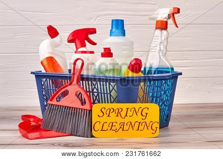 Cleaning Set With Products And Supplies. Plastic Basket With Cleaning Liquids On Wooden Background.