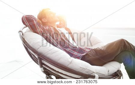 modern guy is resting sitting in a large comfortable chair. side view.