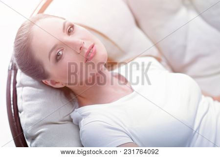 tired woman resting in an easy chair made of rattan