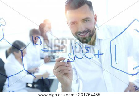 close up of a smiling scientist writes a formula on the blackboa