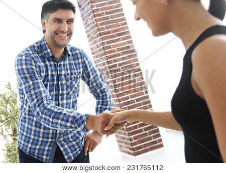Young colleagues shaking hands in creative office
