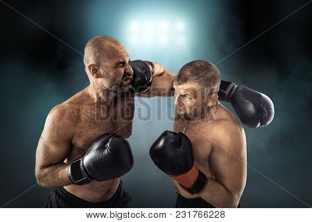 Two professional boxers, athletes in dynamic boxing action on the ring under lights of sport arena.