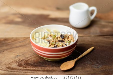 Muesli Cereal With Slice Banana And Milk In A Bowl On Wooden Background, Healthy Breakfast