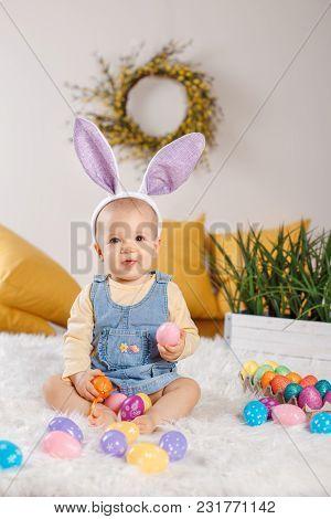 Cute Adorable Caucasian Baby Girl In Jeans Dress Wearing Purple Bunny Ears Sitting In Studio. Kid Ch