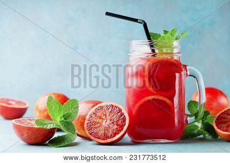 Summer Orange Lemonade Drink Or Juice Decorated Mint Leaves In Glass Jar On Turquoise Background.