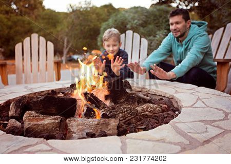 View Of Firepit And Happy Smiling Family Of Two, Father And Son, Warming Their Hands By The Fire And