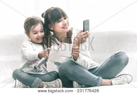 Mom And Daughter Drink Tea On The Couch