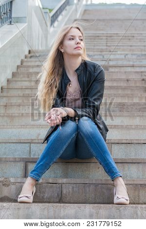 Girl With Blond Hair On The Stairs