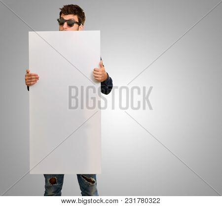 Young Man Holding Banner Wearing Sunglasses On Grey Background