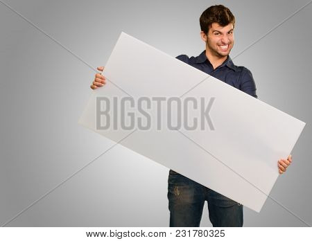 Young Man Holding Banner Gesturing On Grey Background