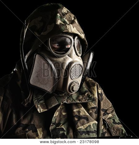 portrait of young soldier with gas mask against a black background