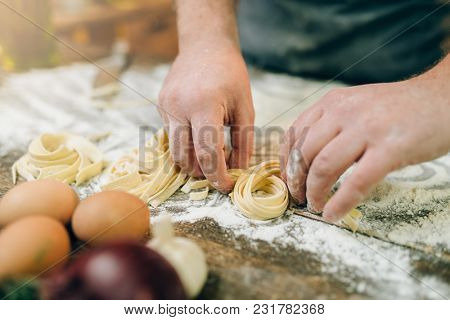Chef hands preparing pasta, fettuccine preparation