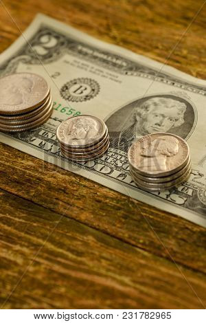Old Banknote Of Two Us Dollars And  Scratched Cents Us Lies On A Vintage Wooden Background. The Conc