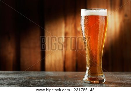 glass with beer on a wooden background