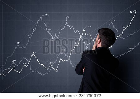 Young businessman in black suit standing in front of a progress chart