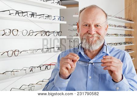Cheerful Elderly Man Choosing Corrective Glasses In Optics Store